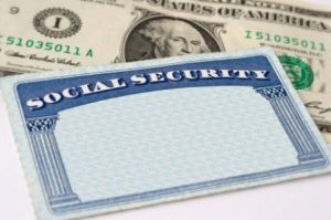Photograph of a social security card with one dollar bill, selective focus.